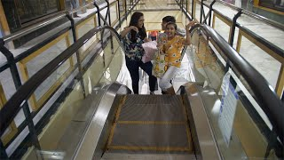Young Indian children coming up from an escalator in a shopping mall - having fun together