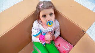 Папа шутит с малышкой в коробке и с игрушками