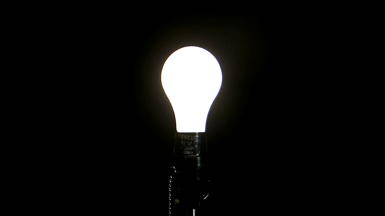 Light Bulb Turning On Against A Black Background HD Stock Footage