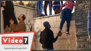 بالفيديو.. شباب يرفعون بنات وسيدات فوق سور جامعة الأزهر لمشاهدة المظاهرات