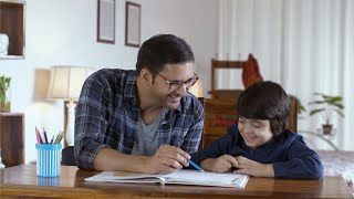 Happy father and son duo in small happy family. A son enjoying studying and doing homework with his father