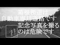 箱根新道路駐して記念写真を撮る老人2人…