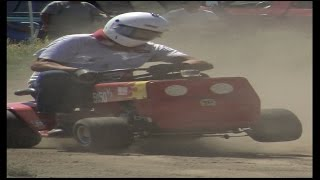 AERIAL AND GROUND FOOTAGE OF EXTREME LAWN MOWERS RACING AROUND AN O...