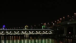 夜の隅田川を渡る東武鉄道の車両