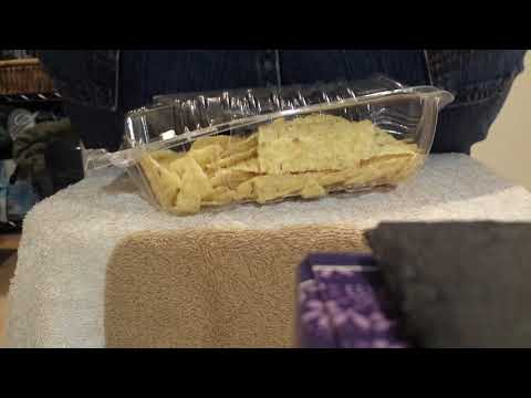 Buttcrushing tortilla chips in a plastic container