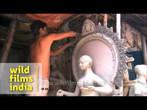 Sculptor working on the completion of clay idol - Kumortuli