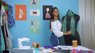 Attractive Indian female designer dressing up a dummy model or mannequin at her workplace