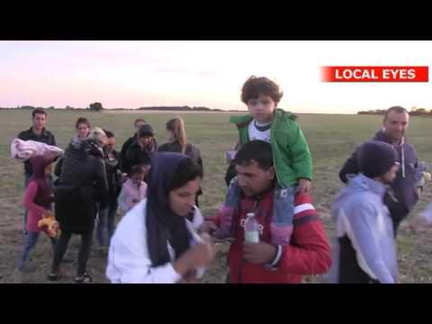 Flygtninge vandrer ud over markerne