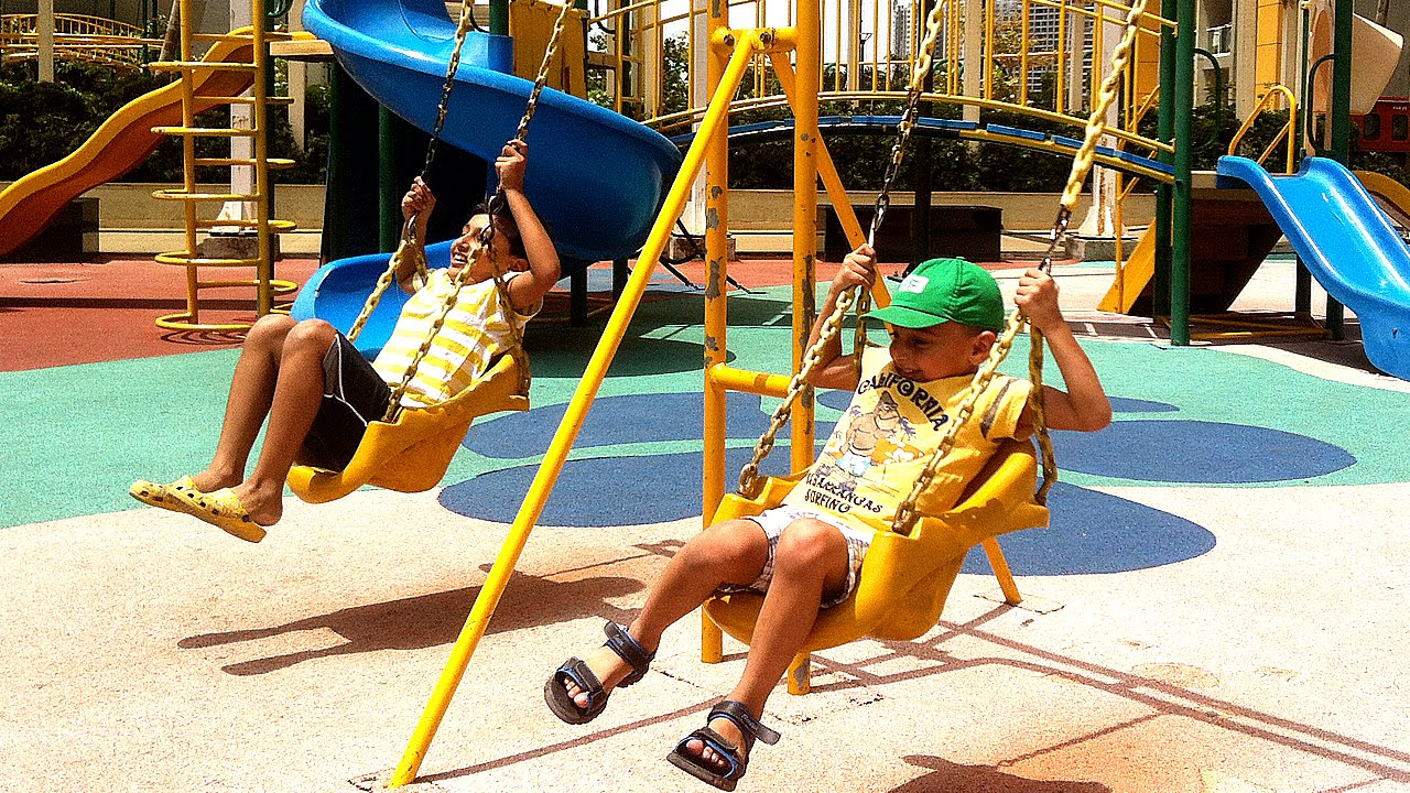 Children Playing In The Park With Slide Swing Rock Wall