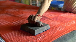 Shot of man block printing on a cotton fabric