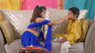 Raksha Bandhan - Cute Indian girl feeding sweets to her brother on Rakhi