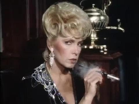 Stella Stevens with long red nails smoking a cigarette
