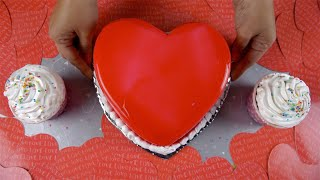 Woman hands placing a heart-shaped cake on a party table for Valentine's day celebration