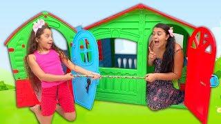 Sarah finge brincar de vizinhas com casas de brinquedos
