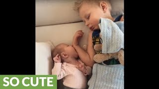 Big brother naps with new baby sister