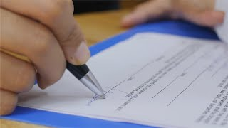 Closeup shot of a business woman / man signing a contract / legal agreement / paper