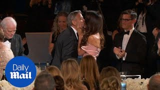 Amal Clooney kisses George as he is honoured by the AFI