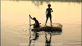 Rag pickers scavenger on raft made of sacking and polystyrene in Yamuna