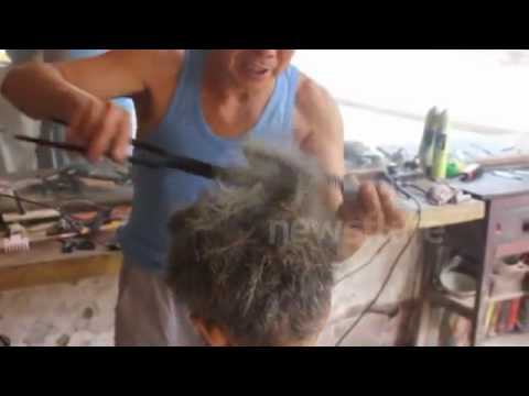 Chinese barber practising the rare art of cutting hair with hot tongs.mp4