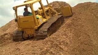 caterpillar d5 dozer moving mulch up a hill