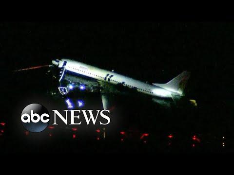 Plane slides off runway into river