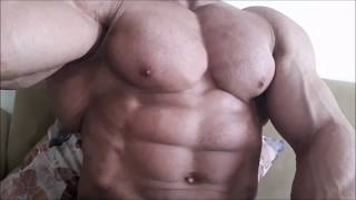 Bodybuilder flexing while seated