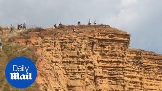 Shocking moment tourists get close to 150ft drop off Dorset cliff