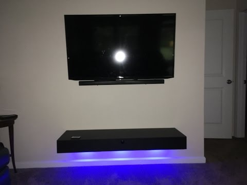 Floating shelf with lights and a door.