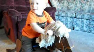 Ilan Riding A Wooden Rocking Horse