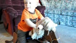 Ilan Riding A Wooden Rocking Horse