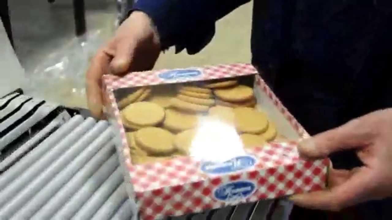 Оборудование для упаковки коробок кондитерских изделий в пленку .
