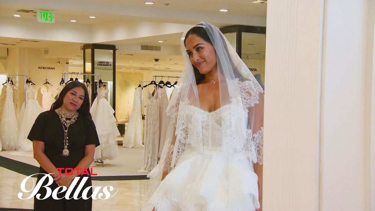 Nikki reluctantly tries on wedding dresses in front of her family ...