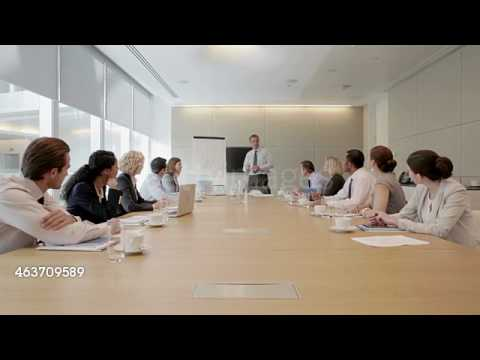 Businessman at flipchart leading meeting in conference room