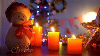 Closeup shot of a cute toy snowman with scented candles burning in a dark room - festive scene