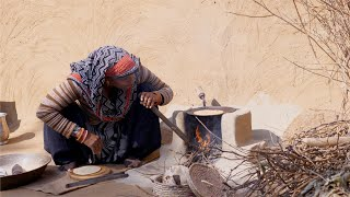 A rural woman blowing with iron pipe into a chulha / traditional wood stove while making roti for her family
