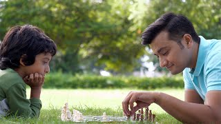 Indian father and son playing chess while spending time together in a park - leisure time