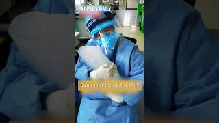 #Medical worker wearing protective suits holds a chunk of ice in her chest to relieve the heat
