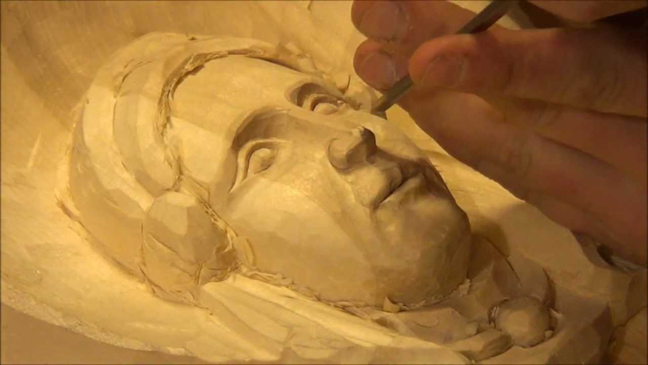 Carving a female face in wood doovi