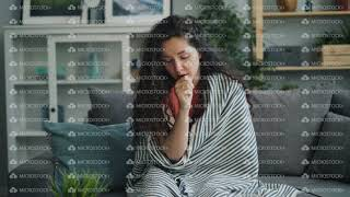 Zoom-in of unhealthy girl coughing and wiping running nose in apartment