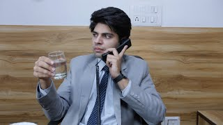 A senior manager of an Indian firm drinking water while having serious discussion on phone