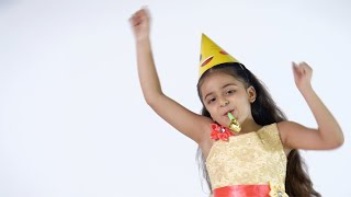 Beautiful Indian kid happily dancing and blowing noisemakers against the white background