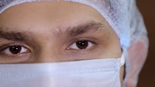 Pan shot of a young doctor in a surgical mask and cap - coronavirus concept