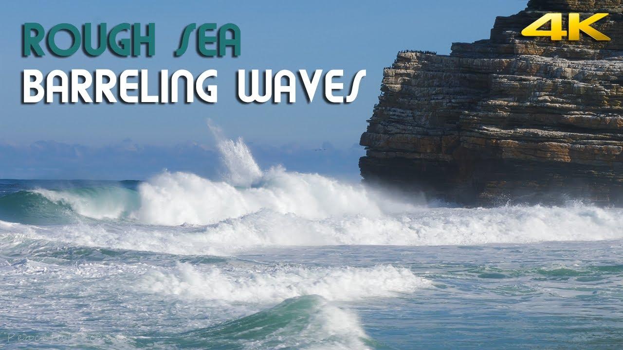 Big ocean waves barreling, crashing and thundering into a small beach   4K  Ultra HD video