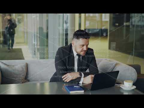 Thoughtful bearded Caucasian businessman sitting and thinking over his business plan while looking