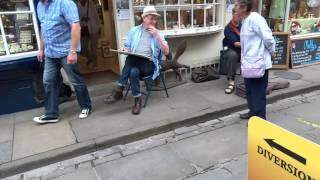 actor and artist Steve Huison sketching in York with guitar by Rod