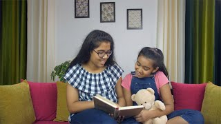 Two Indian siblings happily studying together while sitting on a couch - education concept