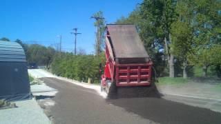 Dump spreading recycled asphalt