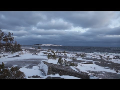 A winter storm sends waves crashing against the rocky shore of the Swedish High Coast