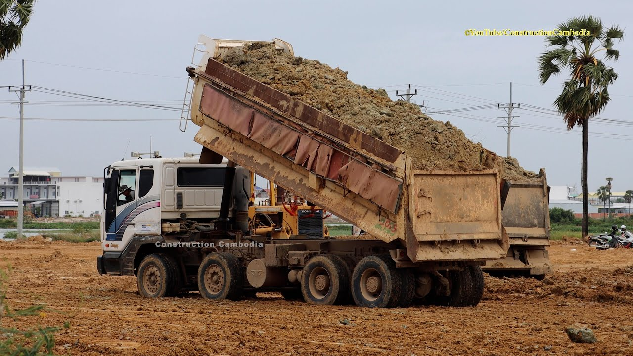 Dump Trucks Dumping a Load of Dirt with Bulldozer Pushing Dirt