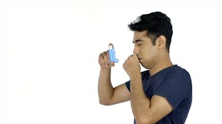 Young asthma patient using a medical spray against the white background in India
